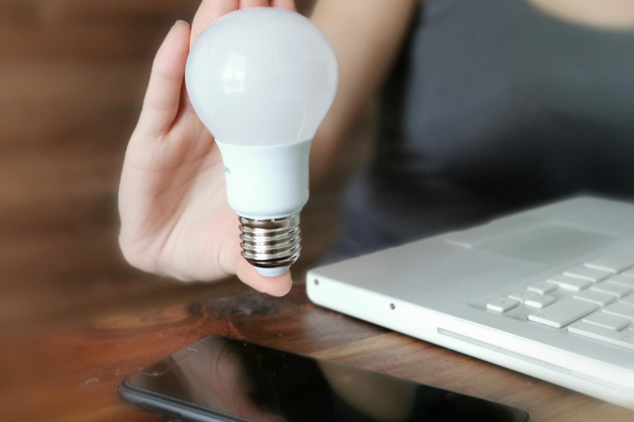 Hier werden eine Glühbirne und ein Laptop für neue Innovationen und Ideen angezeigt