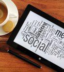 Hier wird ein Kaffee und ein Tablet angezeigt, auf dem Social Media und wichtige Informationen stehen
