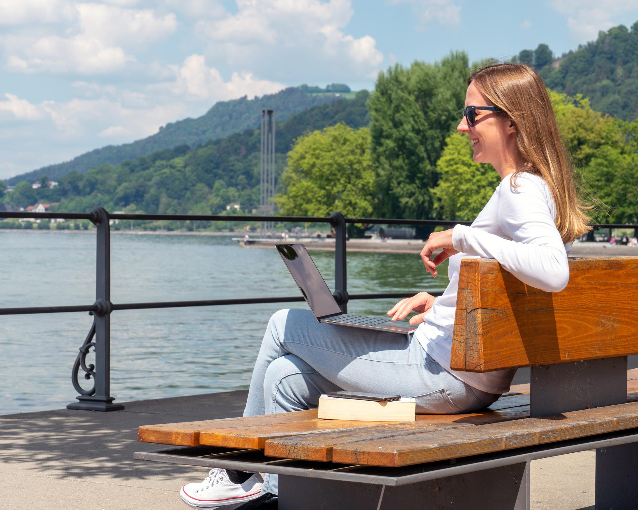 Hier lernt eine Studentin im Frühling entspannt am Wasser